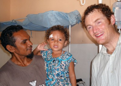 Dr Tom Walker with young girl after removal of cyst
